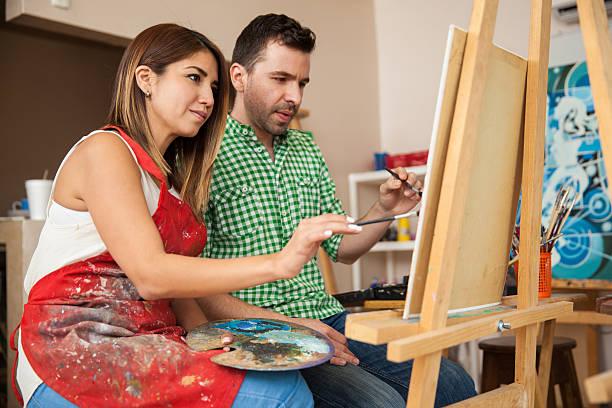 カップルのアーティストが一緒に働く - 美術の授業 ストックフォトと画像