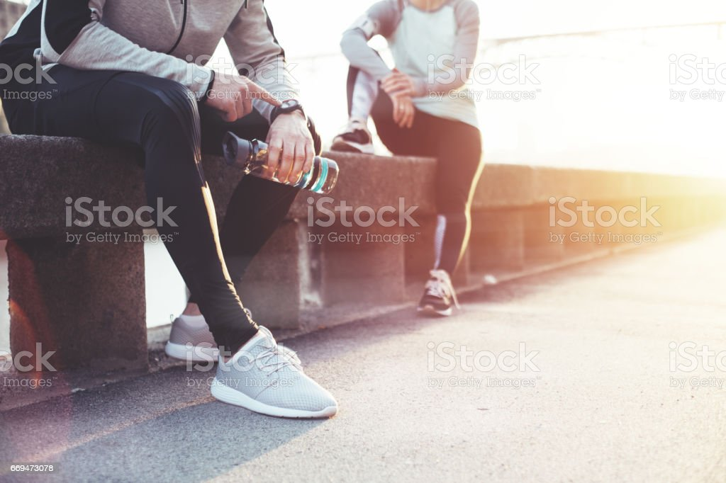Couple of athletes resting after workout on the street stock photo