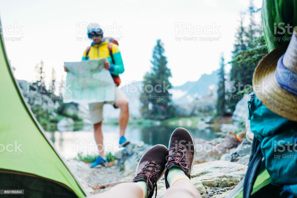 Couple of backpackers hiking and camping in wild stock photo
