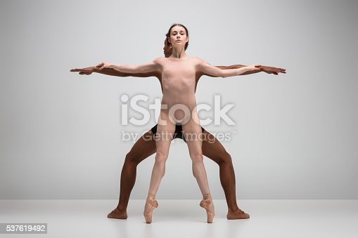 istock Couple of ballet dancers posing over gray background 537619492