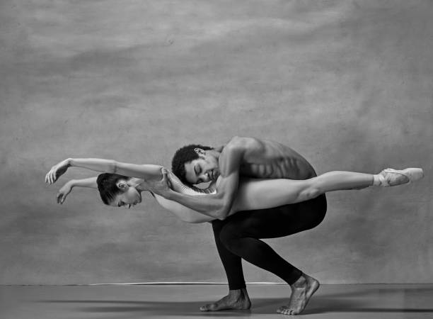 couple of ballet dancers posing over gray background - dance group stock photos and pictures