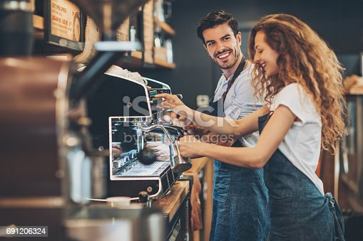 istock Couple of baristas working in a coffee shop 691206324