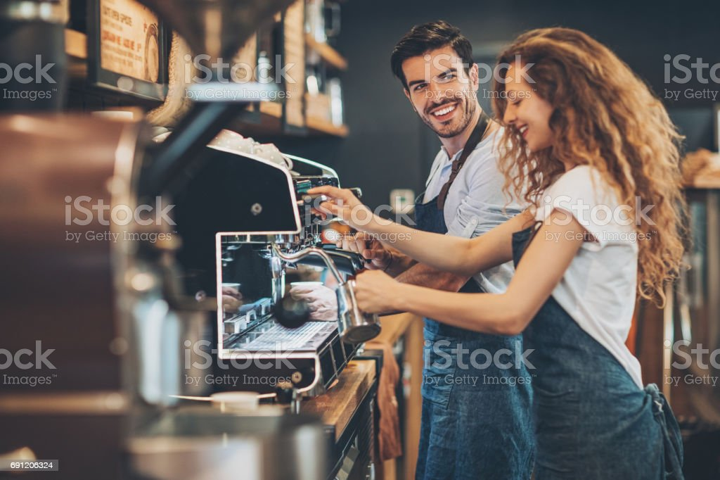 Couple of baristas working in a coffee shop stock photo