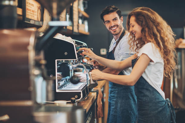 couple of baristas working in a coffee shop - barista stock photos and pictures