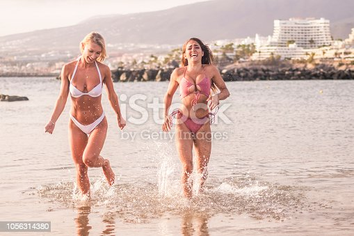 couple of beautiful attractive young women run on the water at the beach and have fun together in friendship. summer vacation under the sun. laugh and smile and relationship