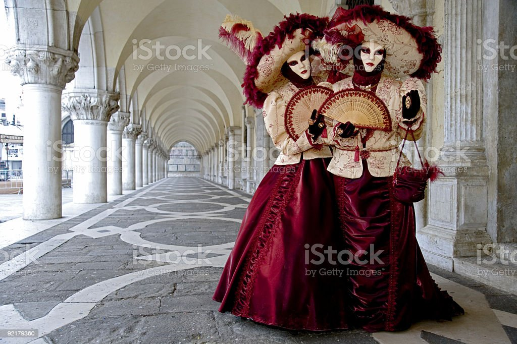 Couple of beautiful female masks under colonnades in Venice (XXL) royalty-free stock photo