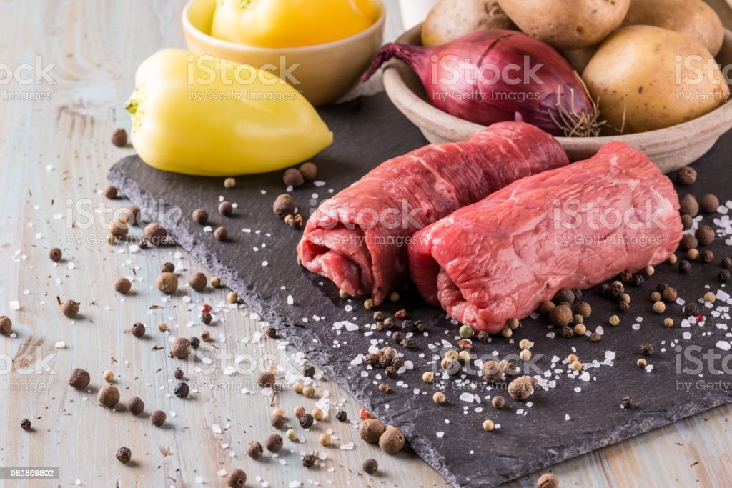 Couple of beef slices prepared for roulade on black slate board stock photo