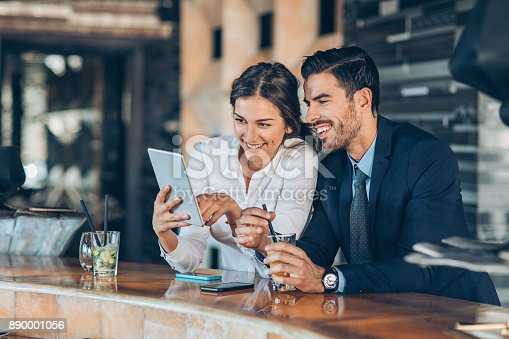 istock Couple of businesspersons having drinks in hotel's lobby 890001056
