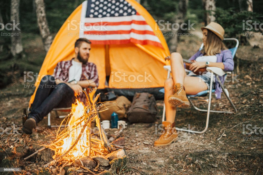Couple of campers relaxing in front of campfire stock photo