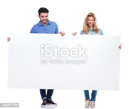 istock couple of casual people presenting a big blank billboard 482021769