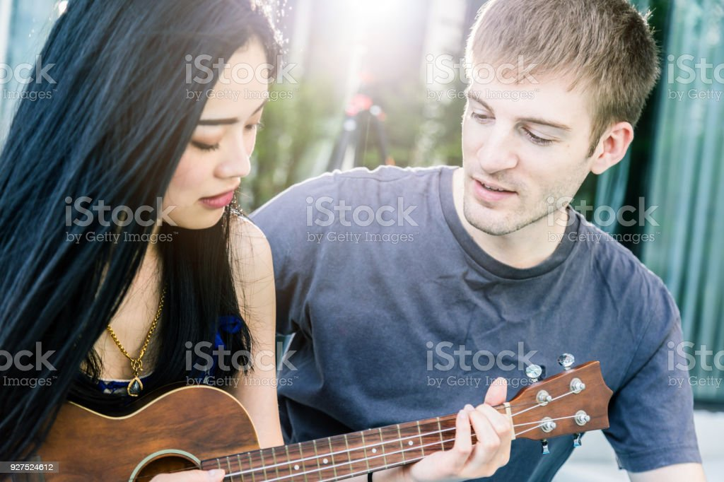 couple of caucasian and asian lover play fun with happiness and joyful and ukulele song outdoor location stock photo