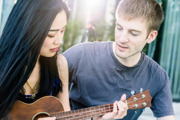 casal de amante de caucasiano e asiático joga divertido com felicidade e alegria e ukulele canção local ao ar livre - foto de acervo