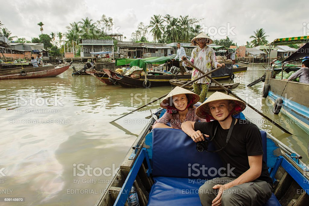 Couple of Caucasian tourists travel to floating market in Vietna - Photo