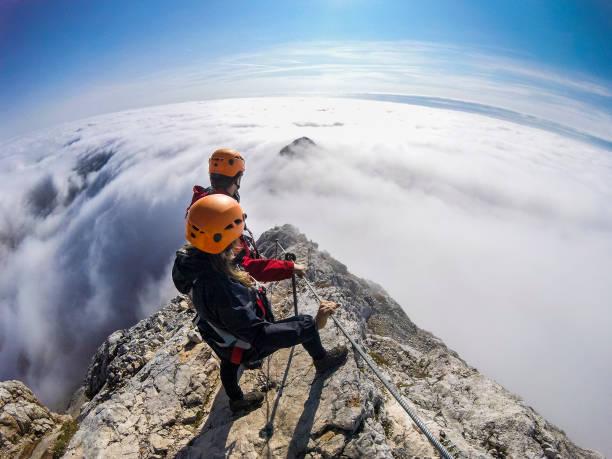 Couple of climbers following via ferrata into a foggy valley stock photo