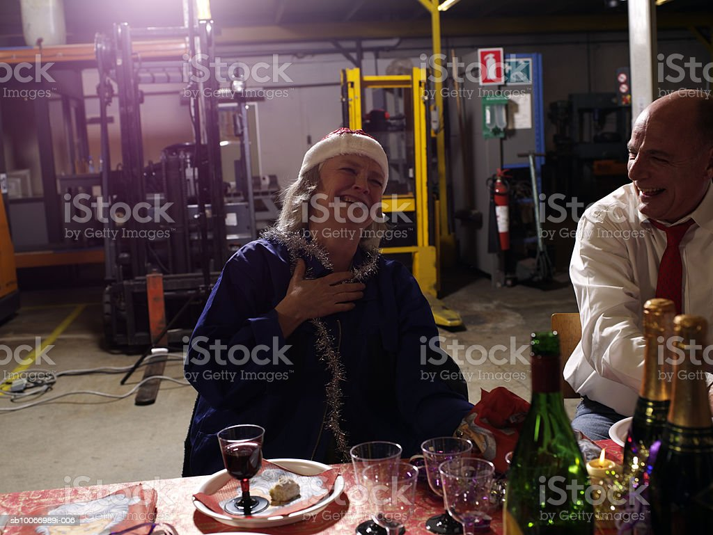 Couple of colleagues laughing at charismas table in warehouse royalty-free stock photo