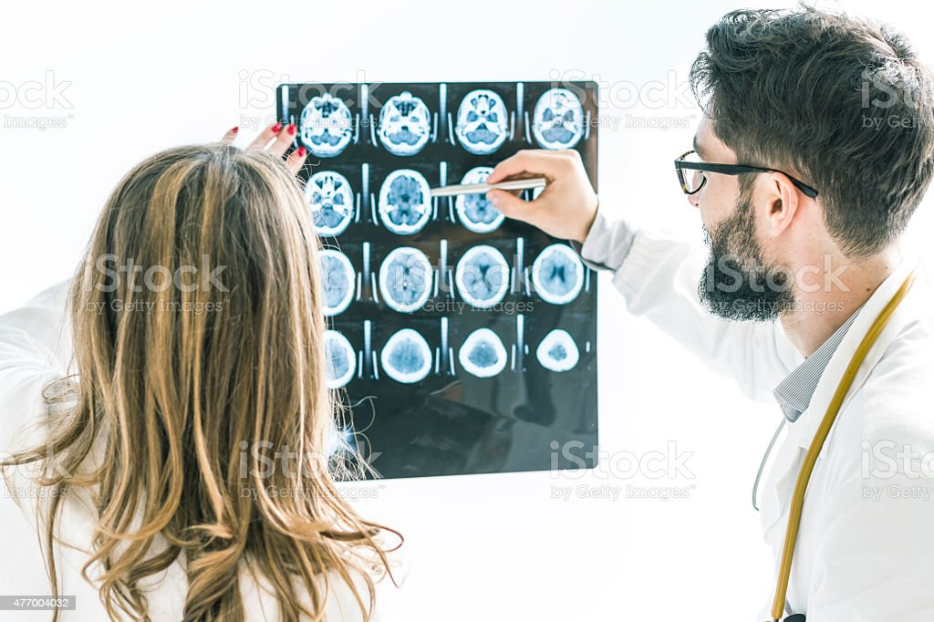 Couple of Doctors examining the x-ray of brain stock photo