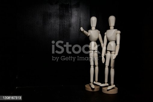A couple of drawing mannequins pointing and watching towards the camera on a black background with copy space