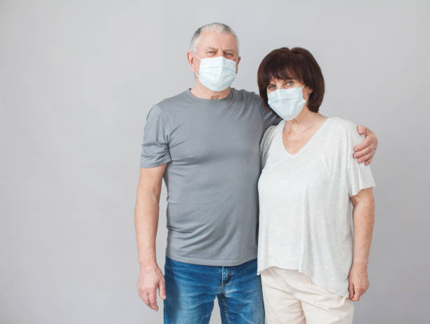 Couple of elderly people in medical masks stock photo