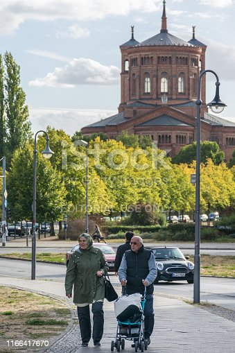 BERLIN, GERMANY - July 28, 2018: Couple of elders walking in a sidewalk with a baby stroller near the Protestant St. Thomas Church, built in 1869 at Mariannenpl, in the Kreuzberg district.