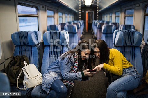 Couple of female friends travel in rail car and watch movie on smartphone.
