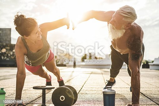 istock Couple of fitness athlete doing workout sessions outdoor at sunset - Happy trendy athlete people training outside - Bodybuilding, empowering and sport concept - Focus on silhouette hands 1059247468