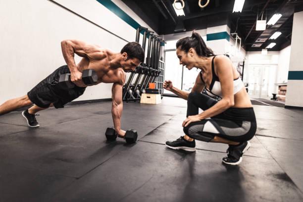 par de modelos fitness haciendo las flexiones - entrenador personal fotografías e imágenes de stock