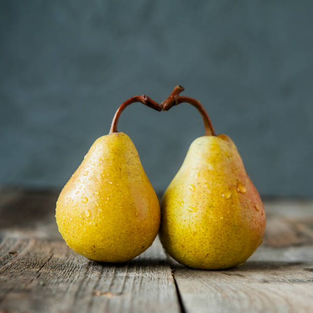 a couple of fresh ripe organic yellow pears form the shape of the heart on rustic wooden table on the dark gray stone background. relations, love. care concept. selective focus, square - pera foto e immagini stock