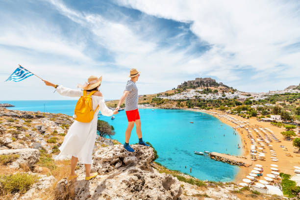 A couple of friends in love with the Greek flag admire the grandiose view of the sea Bay and the beach near the ancient city of Lindos. Honeymoon and travel stock photo