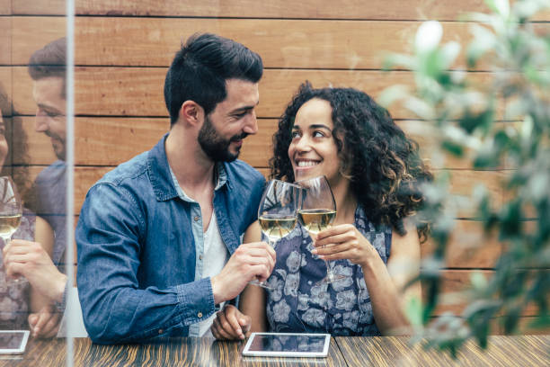 Couple of friends toasting with a glass of wine in a restaurant stock photo