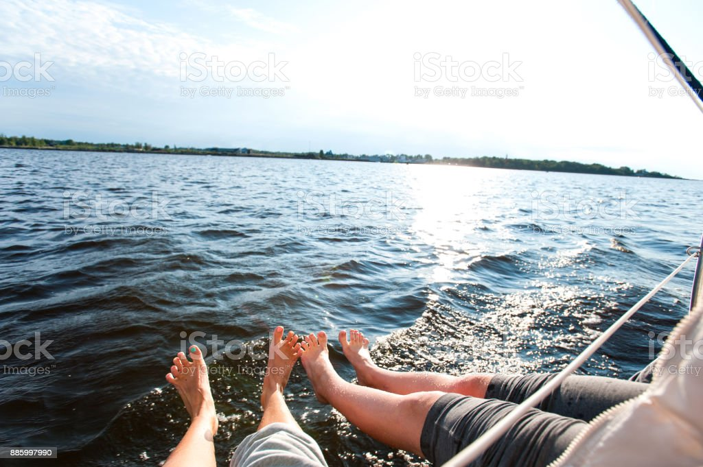 Couple of funny woman feet on sailing boat board stock photo