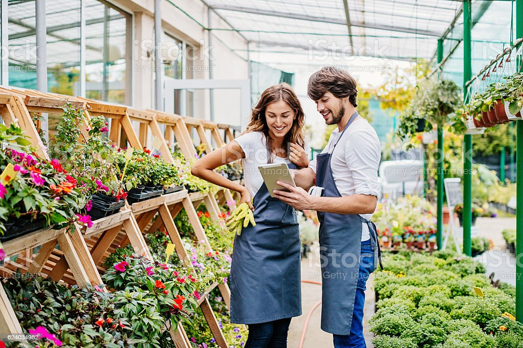 Couple of gardeners with digital tablet stock photo