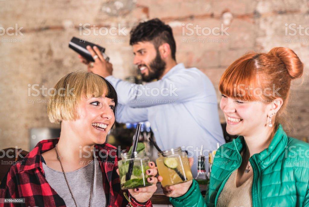 Couple de copines s'amusant à fashion cocktail bar concept Nightlife - barman professionnel secouant boisson derrière la jeune femme ivre - au club de nuit de fête avec des amies fille parler ensemble - Photo