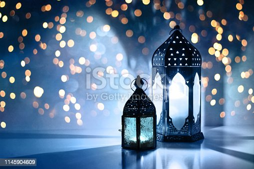 istock Couple of glowing Moroccan ornamental lanterns on the table. Greeting card, invitation for Muslim holy month Ramadan Kareem. Festive blue night background with glittering golden bokeh lights. 1145904609