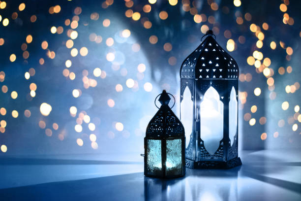 couple of glowing moroccan ornamental lanterns on the table. greeting card, invitation for muslim holy month ramadan kareem. festive blue night background with glittering golden bokeh lights. - eid stock pictures, royalty-free photos & images