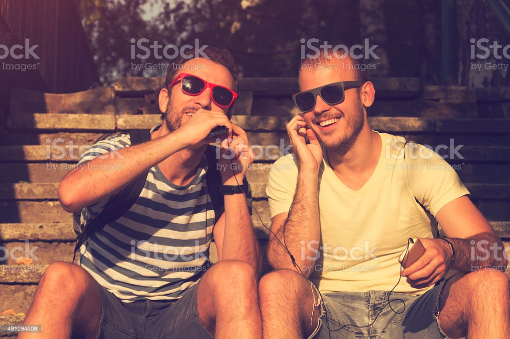 Couple of guys sharing music and singing with a cellphone. royalty-free stock photo