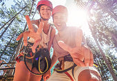 istock Couple of happy climbers having fun in adventure park outdoor - Young friends doing extreme sport - Travel,wanderlust and summer vacation - Focus on faces - Warm filter 837551362
