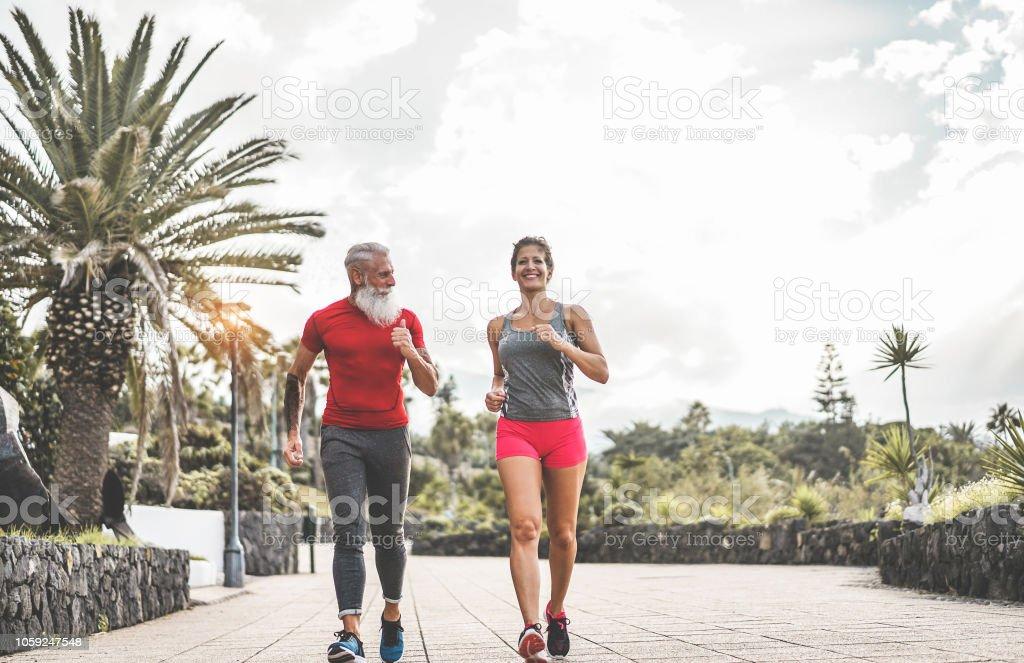 Casal de amigos de aptidão feliz correndo ao ar livre - treinamento em tempo de noite depois do trabalho de pessoas corredores - Jogging e saudável estilo de vida e conceito de esporte - foco principal na cara de homem tatuagem sênior - foto de acervo