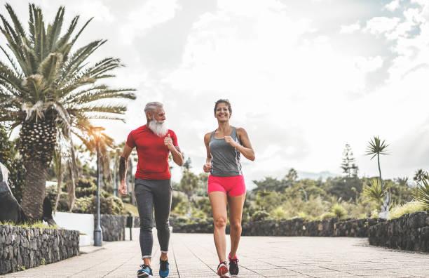 happy fitness freunde laufen im freien - jogger menschen eine ausbildung am abend nach der arbeit - joggen, gesunde lebensweise und sport-konzept - schwerpunkt senior tattoo mann gesicht - alte tattoos stock-fotos und bilder