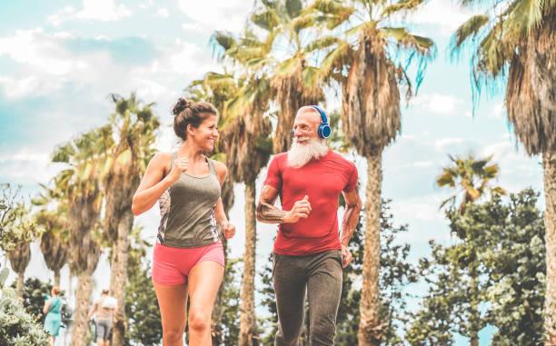 paar happy fitness freunde laufen im freien - im gesicht des mannes jogger menschen eine ausbildung an einem tropischen ort - joggen, gesunde lebensweise und sport konzept - fokus - laufende tattoos stock-fotos und bilder