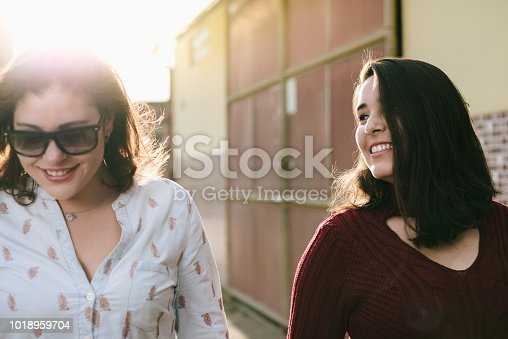 Couple of happy girlfriends walking in the city.
