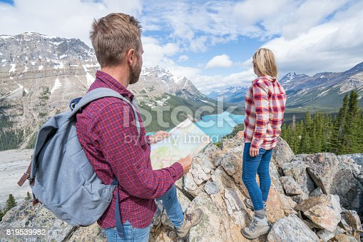 Two young people hiking looking at map in mountain lake scenery.