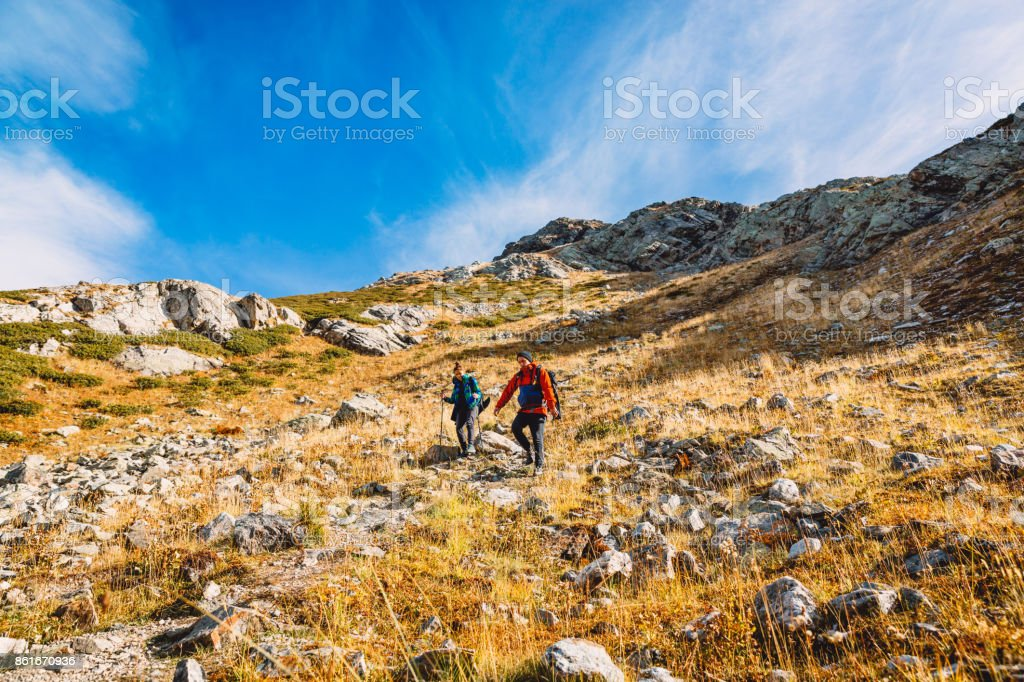 Couple of hikers in the mountains. Tourists descend from the mountain stock photo