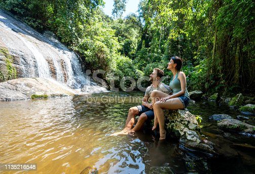 Happy couple of hikers looking at a beautiful waterfall in Brazil and smiling – outdoors lifestyle concepts