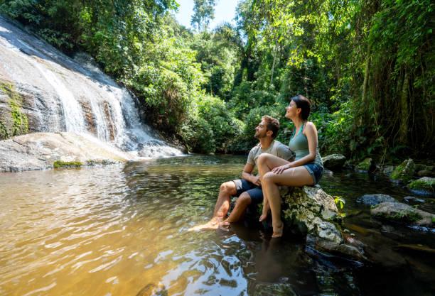 pares de caminhantes que olham uma cachoeira bonita - cascata - fotografias e filmes do acervo