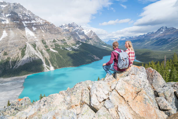 couple of hikers overlooking mountain lake - canada travel stock photos and pictures