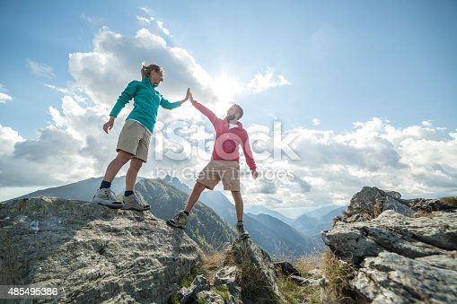 Couple of hikers reaching the mountain top celebrating with a high five.