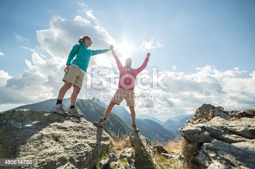 istock Couple of hikers reaching the mountain top celebrating 485614730