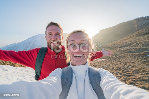 istock Couple of hikers taking selfie portrait on mountain trail 688561528