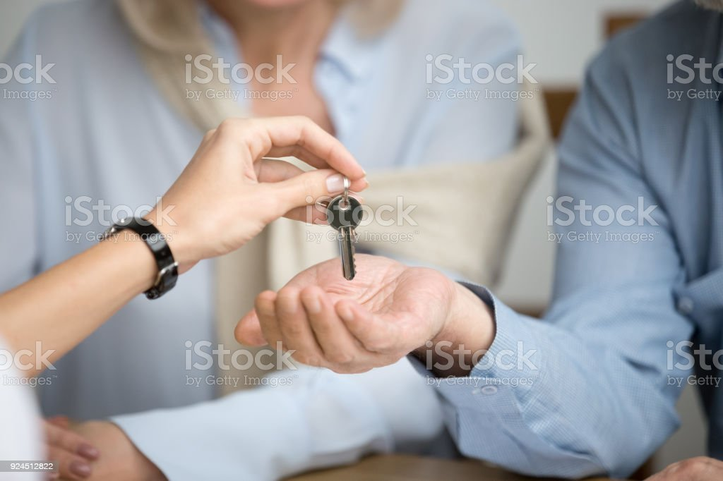 Couple of homeowners getting key to new house from realtor stock photo