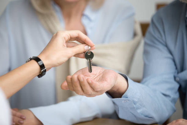 couple of homeowners getting key to new house from realtor - buy a house key imagens e fotografias de stock